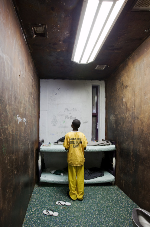 criminalwisdom:  A 12-year-old in his cell at the Harrison County Juvenile Detention Center in Biloxi, Mississippi. The window has been boarded up from the outside. The facility is operated by Mississippi Security Police, a private company. In 1982, a fire killed 27 prisoners and an ensuing lawsuit against the authorities forced them to reduce their population to maintain an 8:1 inmate to staff ratio. Uncompromising Photos Expose Juvenile Detention in America