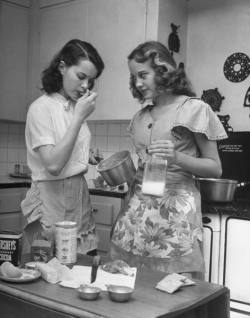 Tulsa Twins Teenager Nancy Churchwell tasting mixture for fudge cake as Barbara Bounds, 17, watches skeptically, while employing their cooking skills in kitchen at Tracy's home. Tulsa, OK, USAugust 1947By Nina Leen