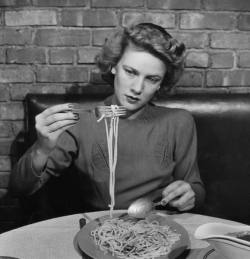 Woman eating spaghetti in restaurant. New York, NY, US1941 By Alfred Eisenstaedt