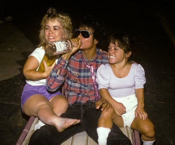 Michael Jackson casually drinking a vodka bottle straight up with two midgets…..no big deal