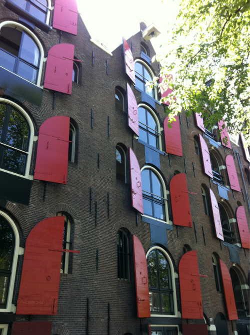 Red shutters, Amsterdam, Netherlands, april 2011. Homesick tonight for my second home. Love the architecture. I'm a dutch girl at heart. Love the vibrant red shutters. I think I snapped this one, thinking it'd be a good way to keep the dangerous daylight from the characters.  Soon, I'll go back.