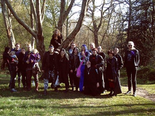 "Bekki submitted this photo with the comment: ""Netgoth picnic, 2002/3, Golders Green London (me holding tiny leopard baby to left of photo"". Only one person up a tree in this shot but we have a lovely supporting cast of netgoths. I just checked the submitted net.goth picnic photo from 1996 and it's THE SAME TREE.  Obviously, this is a tradition.  Where are the photos from other years?  Are there any? If so, send them on in!  I wonder whether we have some of the same goths in both photos? Most of them are smiling, it's a sunny day, the goth up the tree is at a reasonable height. Bonus points for the up-tree tradition.4.2 out of 5 - netgoths off the 'net and up trees"