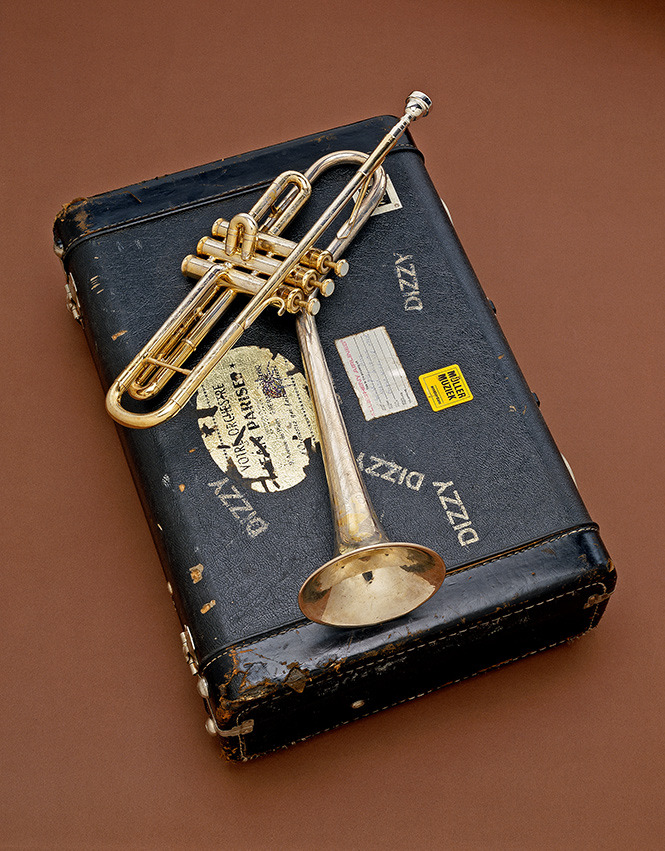 "Dizzy Gillespie's B-flat Trumpet, 1972  This week's Smithsonian Snapshot celebrates Jazz Appreciation Month with American jazz legend John Birks ""Dizzy"" Gillespie's trumpet.    In the 1940s, Gillespie, renowned for his harmonic complexity and scat singing, became a major figure in developing the modern jazz style known as bebop. Gillespie pushed the technical virtuosity of the trumpet, wrote influential compositions, helped introduce Afro-Cuban rhythms into jazz and through his showmanship helped spread the popularity of bebop.    In 1986, Gillespie donated this custom ""Silver Flair"" trumpet, which he played for 10 years, and its custom case to the Smithsonian's National Museum of American History. Its uniquely shaped upturned bell was his internationally known trademark.    Gillespie's trumpet is one of the most iconic instruments in American music; its inclusion in the Smithsonian marks him as one of the most influential and innovative 20th-century American musicians.    To learn more about the importance of jazz in culture, technology, gender and race, visit the Smithsonian's Jazz Appreciation Month 2012 website. To hear musical recordings of Gillespie and other jazz musicians, visit the Smithsonian Folkways' website.    This item is one of 137 million artifacts, works of art and specimens in the Smithsonian's collection. It is on display in the National Museum of American History's Artifact Wall. To learn more about this item, visit the National Museum of American History's website."