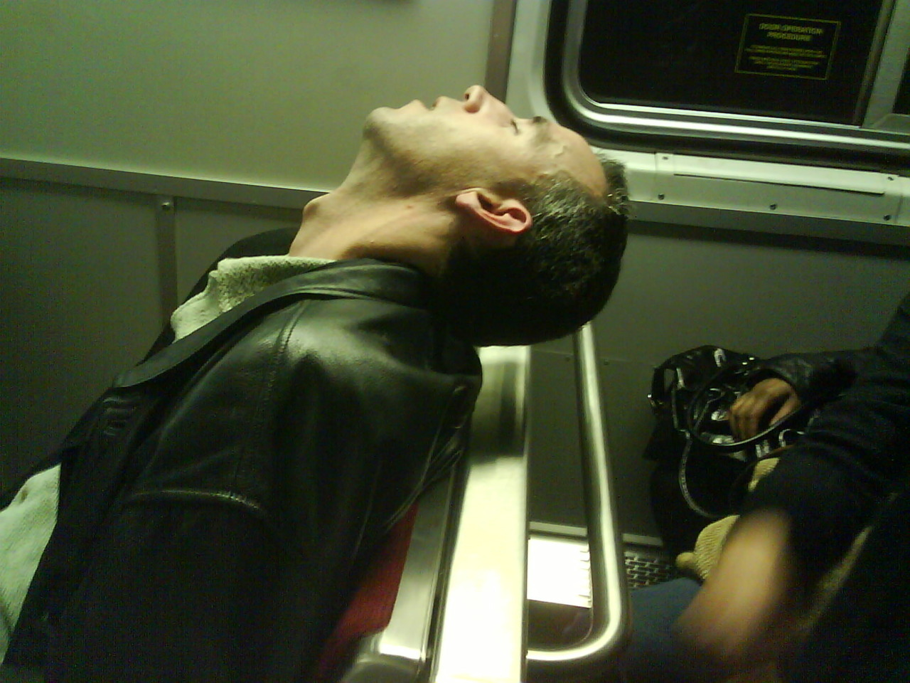 this guy was dead asleep. minutes after taking the photo,  the train braked really hard and his head slammed forward into the glass. it was so loud everyone on the train looked over. he hit it so hard, i don't know how the glass didn't break. - Submitted by Joe