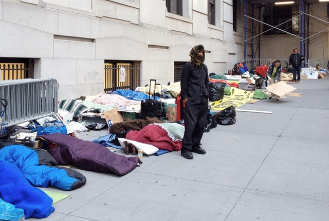 "Wall Street Occupation Shifts From Parks To Sidewalks Near Stock Exchange For the past four nights, protesters affiliated with Occupy Wall Street have camped out on sidewalks near the New York Stock Exchange, sleeping outside banks and handing out literature to financial district workers by day. Why hasn't the NYPD swept in and crushed this dangerous nonviolent political demonstration? It seems Bloomberg's army may be stymied (for now, at least) by a 2000 court ruling upholding protesters' right to sleep on the sidewalk for political purposes, provided they don't take up more than half the sidewalk. Justin Wedes, a spokesperson for Occupy Wall Street, tells us, ""We are bringing the truth about inequity in this country to the belly of the beast, so that the 1%—and the many 99%'ers—who live and work on Wall Street can see what Wall Street's agenda of greed and corruption has done to Main Street."" Last night, according to a new @SleepOnWallSt Twitter feed, over 80 demonstrators spent the night on the sidewalk on Wall Street and Nassau Street. In a video interview, one demonstrator explained further: What we're doing here is kind of a complete return to what we originally planned on doing [at Zuccotti Park]. Union Square was kind of a healing process because we were beaten up and sick of Wall Street. We're still sick of Wall Street. We can handle it in small doses, but now we're back on Wall Street. This time we're not committing any form of civil disobedience, we're in full compliance with the law, we're not disorderly in any way, we're just providing silent messages. And it's a really interesting phenomenon. We'll eventually spread out to all of Wall Street. I kind of think of it like we're a tumor and we're going to keep growing and growing, in a cancerous sense… Of course, capitalism's the real cancer. As the ""Sleep on Wall Street"" cancer spreads to the surrounding area in the Spring weather, it will be interesting to see how Bloomberg and NYPD Commissioner Ray Kelly react. After all, the NYPD has no problem acting extra-judicially to stifle dissent and dealing with the fallout in court later. If they lose, the City can always just cut a check to settle any pesky lawsuits! But down in DC, Occupy protesters camping outside banks have already been dragged off in handcuffs for engaging in ""sleepful protest."" Source"