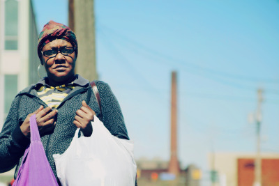 "COOKIE — A homeless woman who goes by the name ""Cookie"" walks from the Bishop Cosgrove Center in downtown Cleveland on April 13, 2012. Cookie said she went to the center, which is operated by Cleveland Catholic Charities, to receive a free meal. ""It's a blessing for people who can't afford a living and don't have family,"" Cookie said. She stays most nights at the Norma Herr women's shelter on Payne Avenue. Photo by Brandon Blackwell @CapturedCLE"