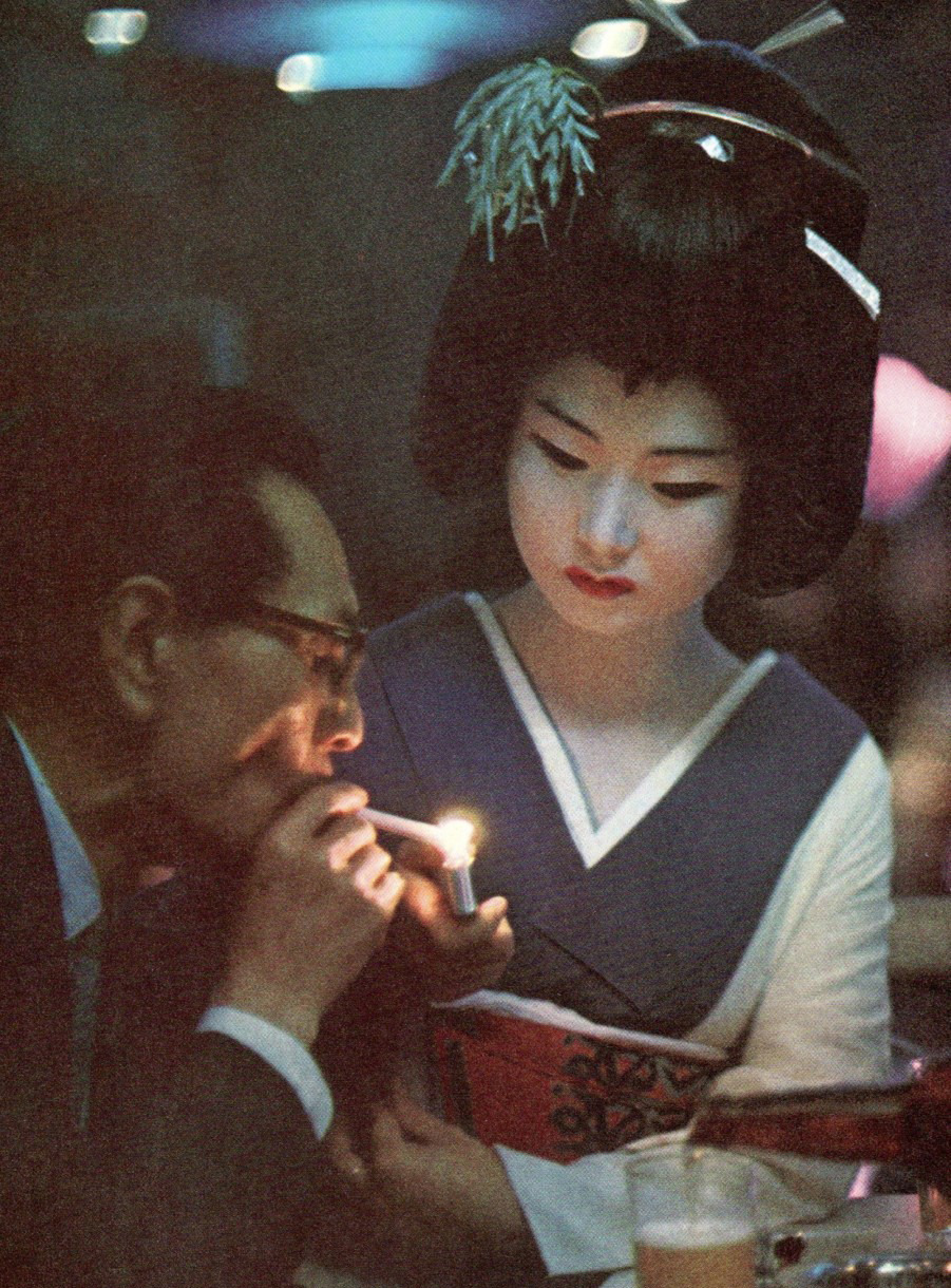 math-letics:  Geisha presents a light to a diner in a Tokyo restaurant, 1969.