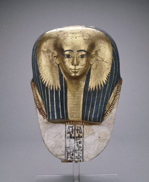 "Mummy mask, Early 18th Dynasty Ancient Egypt, 1500 BCE ""Cartonnage mummy-mask of Satdjehuty: on this splendid female mask, gold leaf not only covers the woman's face, but also her huge collar necklace and the vulture-headdress that embrace the front and sides of her voluminous, lapis lazuli-coloured wig. The wings are examples of protective symbolism that, like the feather patterns on many anthropoid coffins of the Seventeenth and early Eighteenth Dynasties, evokes the guardianship of Isis and other deities. This woman's name, once written at the bottom of each column of hieroglyphs, has been lost. There are two columns of hieroglyphic text on the chest."" The British Museum"