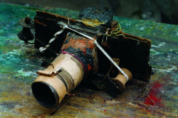 "Miroslav Tichý's homemade camera ""He fashioned various ones from shoe-box cardboard, tin cans, cigarette boxes, toilet paper rolls, and elastic string. His lenses were Plexiglas rounds polished with ash and toothpaste."""