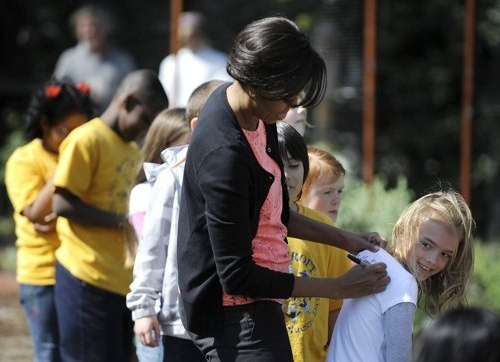 "My cousin's youngest daughter Evan Bay got to meet Michelle Obama at the White House Kitchen Garden planting last month.  Eva Kumsher, Evan Bay Brakke and Caroline Maifield teamed up with White House assistant pastry chef Susie Morrison to plant onions. As the planting job wrapped up, Evan Bay took a moment to let Mrs. Obama know they shared something else in common. ""We've got the same dog as you,"" she said. Mrs. Obama asked if her Portuguese water dog had curly hair like the Obamas' dog, Bo. It does, Evan Bay said of Nala, her family's pet. After posing for a picture with all the students, Mrs. Obama signed school T-shirts that the students had worn to the event.  (pic / article / whitehouse.gov)"