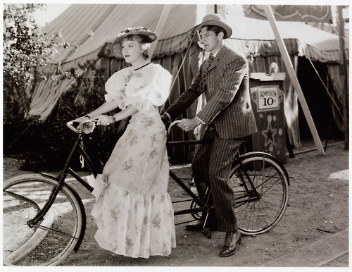 Fay Wray and Gary Cooper riding a bike.