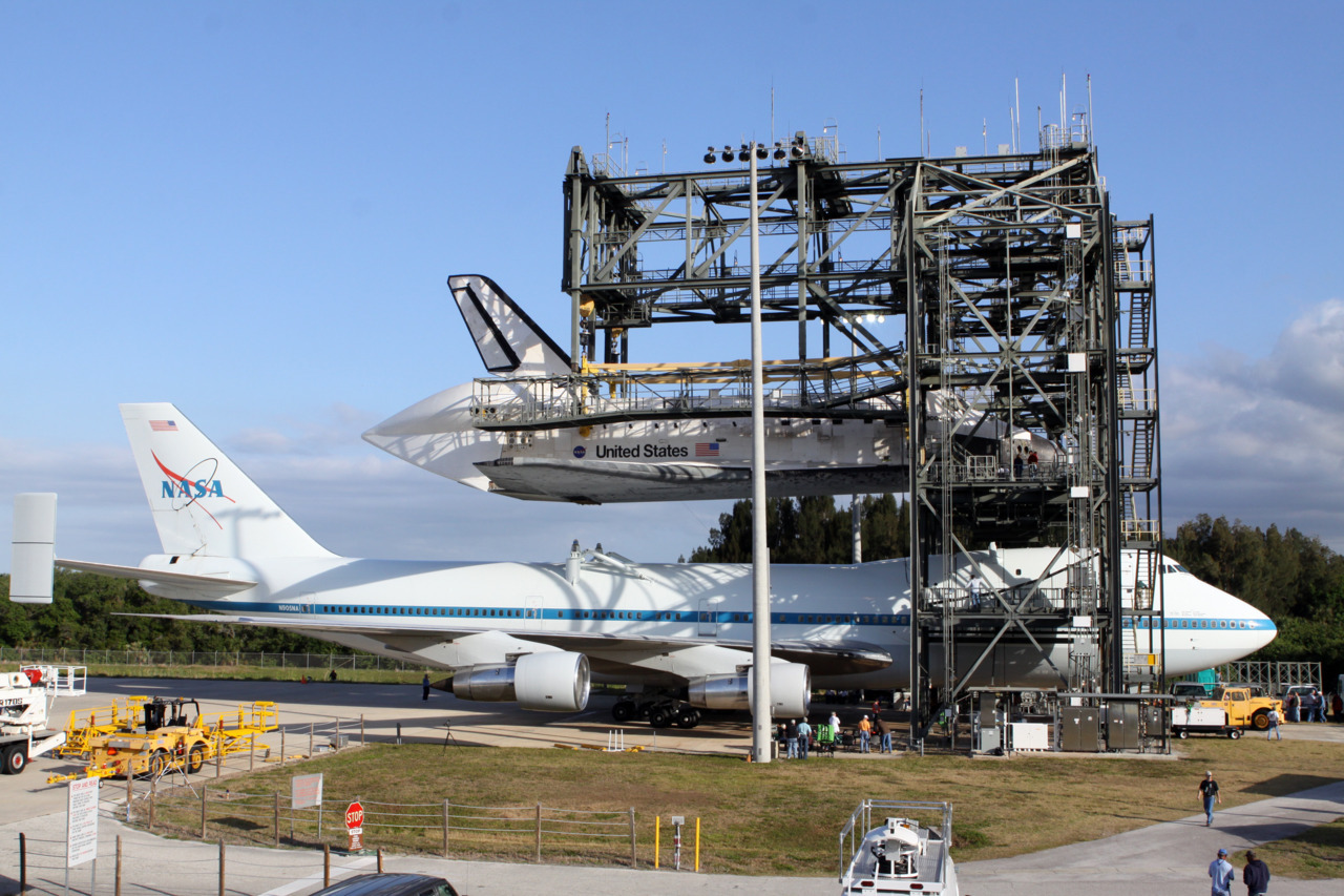 At the Shuttle Landing Facility at NASA's Kennedy Space Center in Florida, the Shuttle Carrier Aircraft is positioned beneath space shuttle Discovery in the mate-demate device. Discovery will be lowered and mated to the aircraft in preparation for its departure from Kennedy on Tuesday. The device, known as the MDD, is a large gantry-like steel structure used to hoist a shuttle off the ground and position it onto the back of the aircraft, or SCA. The SCA is a Boeing 747 jet, originally manufactured for commercial use, which was modified by NASA to transport the shuttles between destinations on Earth. The SCA designated NASA 905 is assigned to the remaining ferry missions, delivering the shuttles to their permanent public display sites. NASA 905 is scheduled to ferry Discovery to the Washington Dulles International Airport in Virginia on April 17, after which the shuttle will be placed on display in the Smithsonian's National Air and Space Museum Steven F. Udvar-Hazy Center.