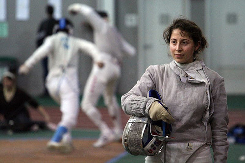 modernfencing:  [ID: a sabre fencer with her mask off, looking down the strip.] Louisa Zouein! She graduated before I came to Tufts, but she came back this year to be our assistant coach. A super helpful and fun person to be around, just saying. (Photo credit: Aaron Donovan.)