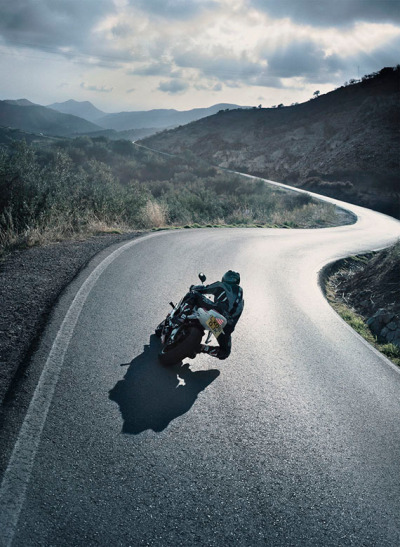 Where I'd really like to be- in the seat of a bike going through twisties. (Would love to know who photographed this…)