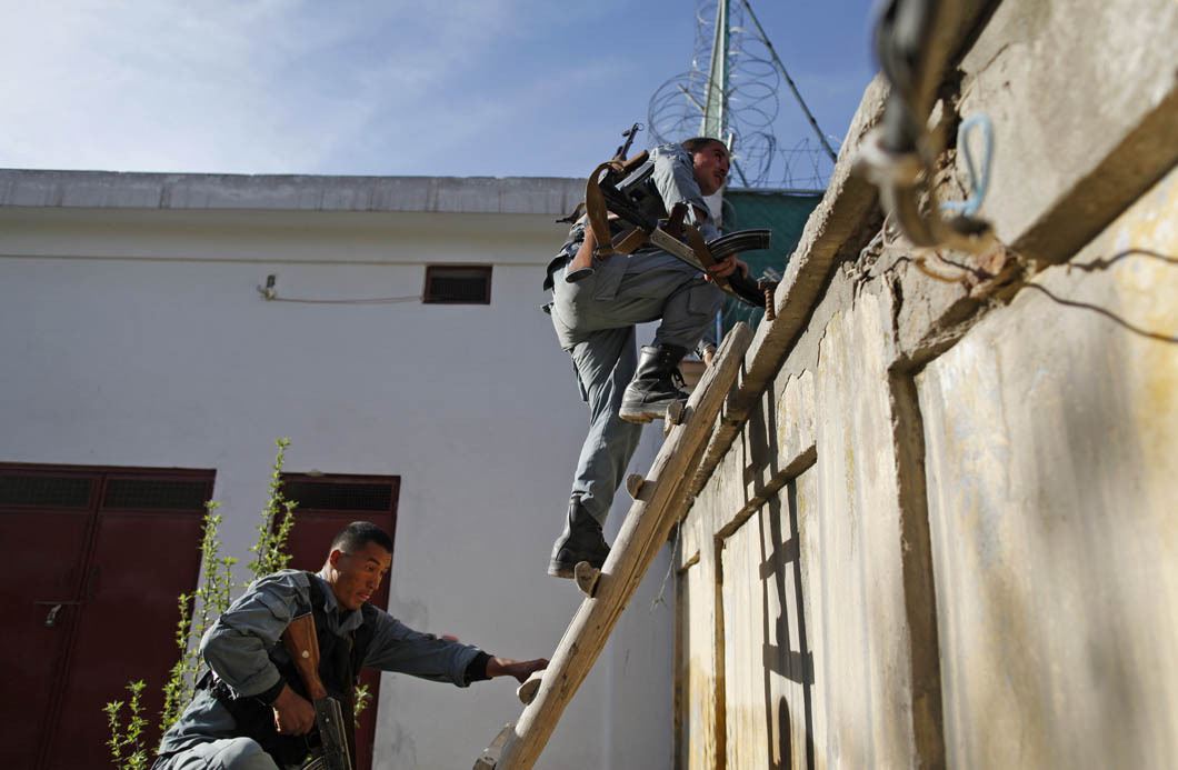 Afghan police climb over a compound wall during heavy fighting in support of an Afghan Special Forces sniper firing on insurgents holed up in buildings near the Wazir Akbar Khan neighborhood of central Kabul. Soon after, the bodies of their comrades were taken out of the compound. Photo: Javier Manzano The war in Afghanistan is not over. Help us tell the story. Fund our Kickstarter.