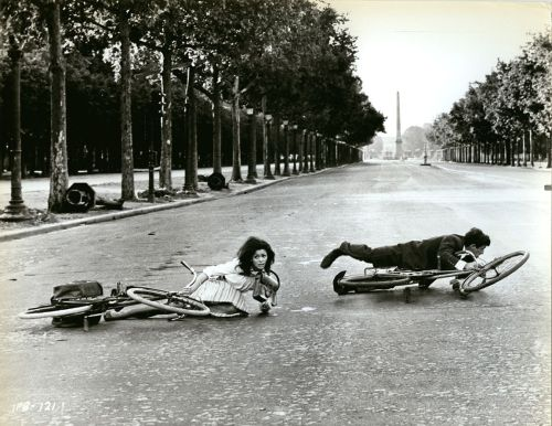 Marie Versini and Jean-Paul Belmondo crawl with bikes.
