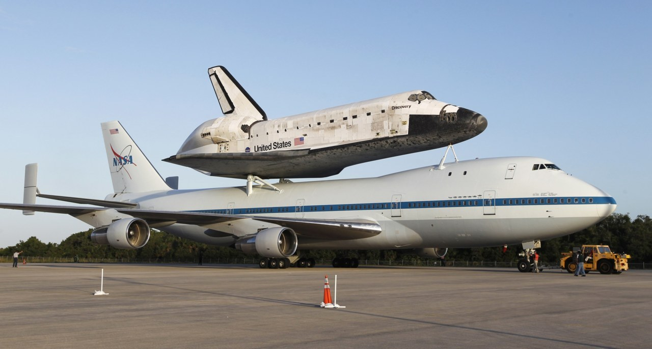reuters:  The space shuttle Discovery is shown attached to a modified NASA 747 aircraft at Kennedy Space Center in Cape Canaveral, Florida April 16, 2012. Discovery is expected to be flown to its final home at the Smithsonian National Air and Space Museum Steven F. Udvar-Hazy Center in Chantilly, Virginia on April 17. [REUTERS/Joe Skipper]   This must have taken a million bungee cords/twine to secure.