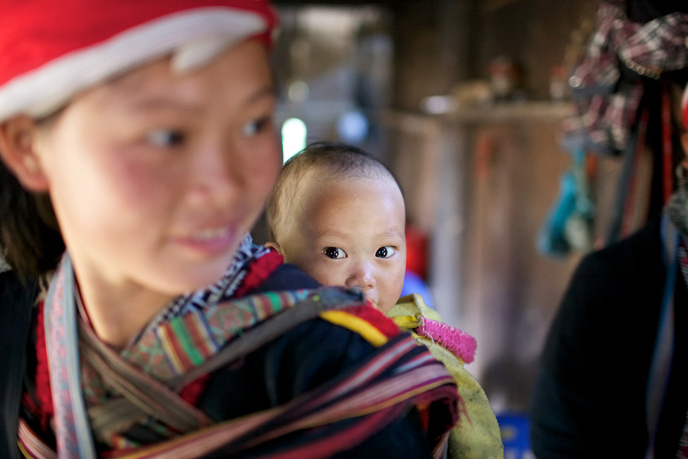 A woman of the Red Dao Ethnic Minority People of Vietnam carries baby on her back in Ta Van Village, Vietnam Photograph by Stephen Bures (Ho Chi Minh City, Vietnam), November 2011, Ta Van Village, Vietnam
