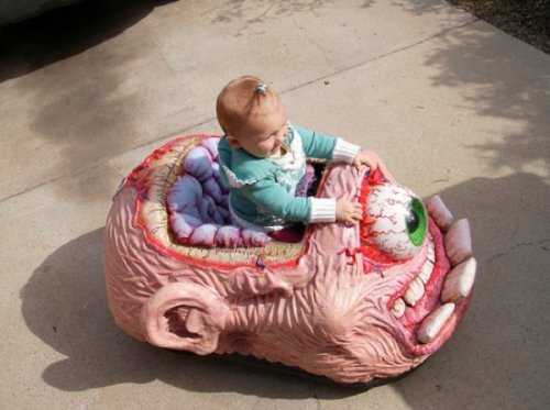 Child Sits in Terrifying Toy   Or maybe it's a monster thinking of a baby. I have no idea what's going on here.