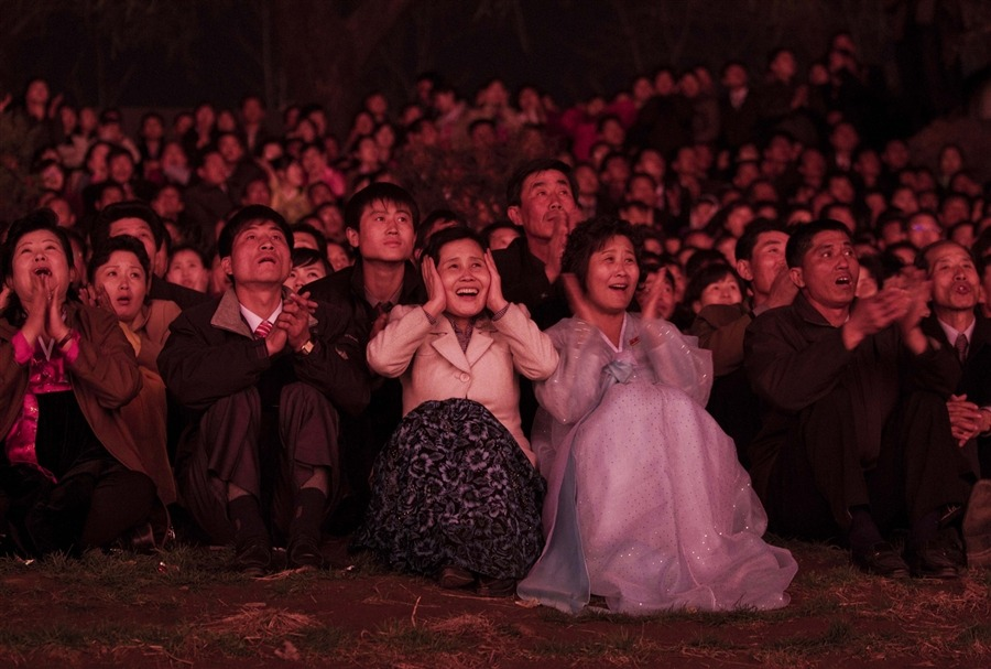 North Koreans, lit with red light, look on with delight as they watch a fireworks display along the Taedong River in Pyongyang to celebrate 100 years since the birth of the late North Korean founder Kim Il Sung on April 15. [Credit : David Guttenfelder / AP]