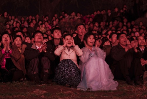 fotojournalismus:  North Koreans, lit with red light, look on with delight as they watch a fireworks display along the Taedong River in Pyongyang to celebrate 100 years since the birth of the late North Korean founder Kim Il Sung on April 15. [Credit : David Guttenfelder / AP]