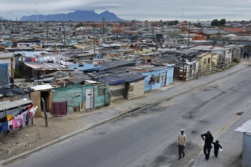 """I was completely bowled over by Khayelitsha. Khayelitsha's poverty is a harsh smack across the face – it's the largest township in South Africa and it's predominantly shanty villages made of scrap metal and pieces of decaying timber. Gang wars rage unchecked – almost everything is riddled with bullet holes – and crimes against women have reached epidemic levels. Kids wearing clothes that don't fit them entertain themselves by playing in the dust. 60% of the adult population is unemployed, so some men and women whittle away their days by wandering streets drunk or high off 'Tik' – a substance much like Crystal Meth that literally eats away at your brain. Despite the ever-present South African resilience and determination, there is discontent directed towards an incompetent government and an overwhelming sense of helplessness; simmering just beneath the surface of the township. It is both devastating and utterly fascinating. I was terrified that we were going to get car-jacked every time we stopped at a red light – and yet I can't wait to go back there. I'm a moth lured to flame; completely intrigued by the one place that I'm guaranteed to die if I wander around it alone."" - except from my daily journal on 4th April 2012."