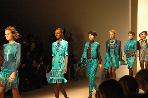 HOLLY FULTON AW12 It was one of the most anticipated shows of the day. Streams of people queued in the courtyard, trying and get themselves a seat for a glimpse of the Holly Fulton show.  Known for her exquisite jewellery, Fulton has secured herself a legion of fans ever since launching her range in 2009. After quite a kerfuffle of trying to get into the show space, we took our seats, the lights were dimmed and an explosion of colour was unleashed. Bright pinks and blues strode out onto the catwalk, teamed with geometric patterns and interesting cuts. Classic layering worked in harmony with multi-toned black and blue shades, whilst the accessories added and eye catching aesthetic.   Each outfit was styled with Fulton's signature bold jewellery, and the occasional simple clutch bag. The favourite accessory of the show was undoubtably the black furry tote bag, which complimented the sophistication of the garment.  There was a hint of Versace with the bold pinks and blacks, but Fulton made it her own by mixing her signature modern materials with intense graphic prints. Excelling in quality and style, the only let down during the show was the restriction on colour, as we would've loved to have seen some experimentation with oranges and reds.  The show was a psychedelic dream, taking us on an adventure through the workings of Fulton. There wasn't a dull moment, and we can only hope to see more of this eclectic work in the next season.