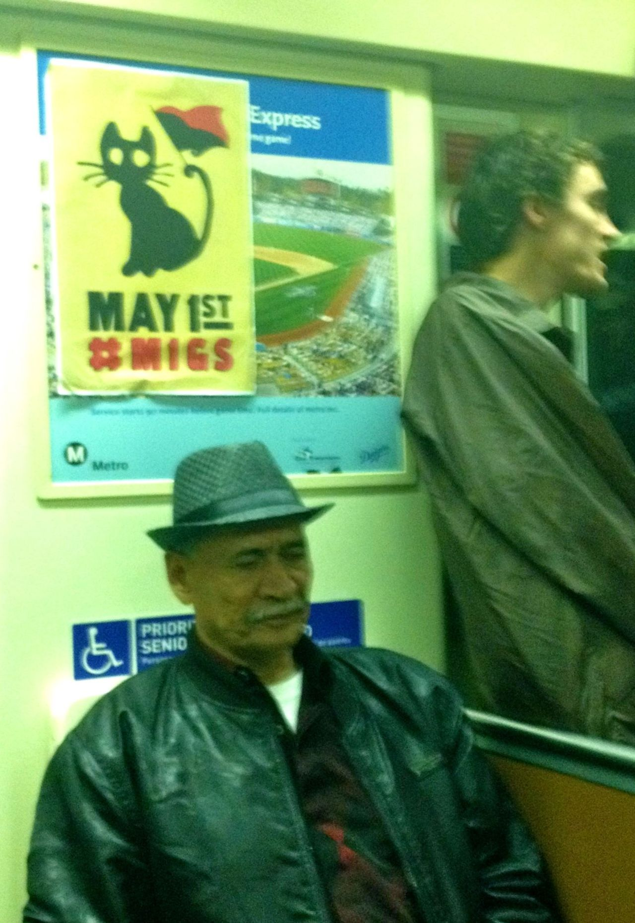 streetartsdistrict:  A stylish old man dozes on an L.A. subway car Sunday evening after youths put up a poster for the May 1 Occupy event happening in the city and elsewhere. I snagged a copy of the cat poster, which I really like.  From the standpoint of communication revolutions, I'm particularly fascinated that the poster contains such sparse information, just a date and a Twitter hash tag. Those who check out #M1GS will finds lots of talk and connections for Occupy events on May 1 around the country. Fascinating.