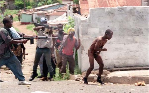 "gunrunnerhell:  Covering your junk ain't going to save you… (Liberian fighters execute a rival that they captured and stripped naked. They're using Belgian FAL rifles. As horrible as war is, it can get worse. During the Liberian War, cannibalism did occur. There was even a child soldier unit that would eat the testicles of their enemies; a snack they called ""Man-wich"". Cannibalism is rooted with tribal beliefs that it made a warrior stronger and children believed it.)  They're shooting him wrong."