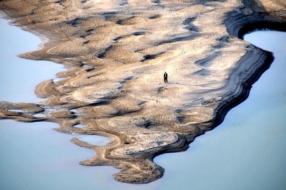 climateadaptation:   A man stood on the exposed shoal of the Hanjiang River Monday, April 16, 2012. A lack of rainfall has contributed to a severe drought throughout Hubei province, China.  [Credit : Cheng Fuhua/Xinhua/Zuma Press]