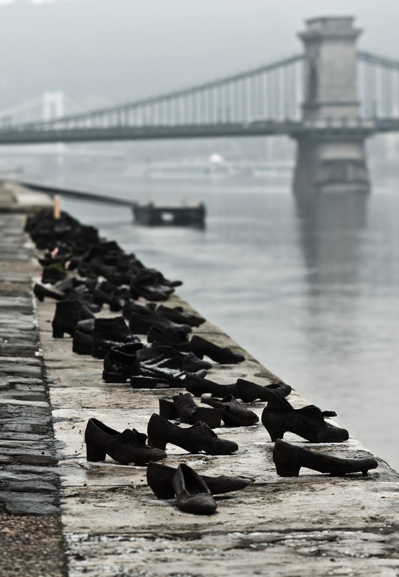 "© Nikodem Nijaki, Jan. 1, 2012, Shoes on the Danube Promenade - Holocaust Memorial, Budapest The Shoes on the Danube Promenade is a memorial created by Gyula Pauer and Can Togay on the bank of the Danube River in Budapest. It honors the Jews who were killed by fascist Arrow Cross militiamen in Budapest during World War II. They were ordered to take off their shoes, and were shot at the edge of the water so that their bodies fell into the river and were carried away. It represents their shoes left behind on the bank. The sculptor created sixty pairs of period-appropriate shoes out of iron. The shoes are attached to the stone embankment, and behind them lies a 40 meter long, 70 cm high stone bench. At three points are cast iron signs, with the following text in Hungarian, English, and Hebrew: ""To the memory of the victims shot into the Danube by Arrow Cross militiamen in 1944–45. Erected 16 April 2005."" (read more) (thanks to / via: only-i-can-live-forever)"