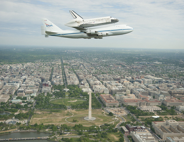 usagov:  Image description: This morning the Space Shuttle Discovery took a final flight around Washington, D.C. perched on top of a 747 jet before being transferred to its final resting place in the National Air and Space Museum's Udvar-Hazy Center in Virginia. The remaining space shuttles will be transferred to various museums and visitors centers throughout the country. Space Shuttle Enterprise is scheduled to head to New York on April 23. Space Shuttle Atlantis will be moved to the Kennedy Space Center in Florida, with the new visitor center to open as early as summer 2013. Space Shuttle Endeavour will rest in the California Science Center in Los Angeles, tentatively slated to happen in later 2012. Learn more about NASA's special 747 jet that transfers the shuttles after their missions are complete. If you were in DC today and saw the shuttle fly by, you can share your photos from the event. Photo by NASA.