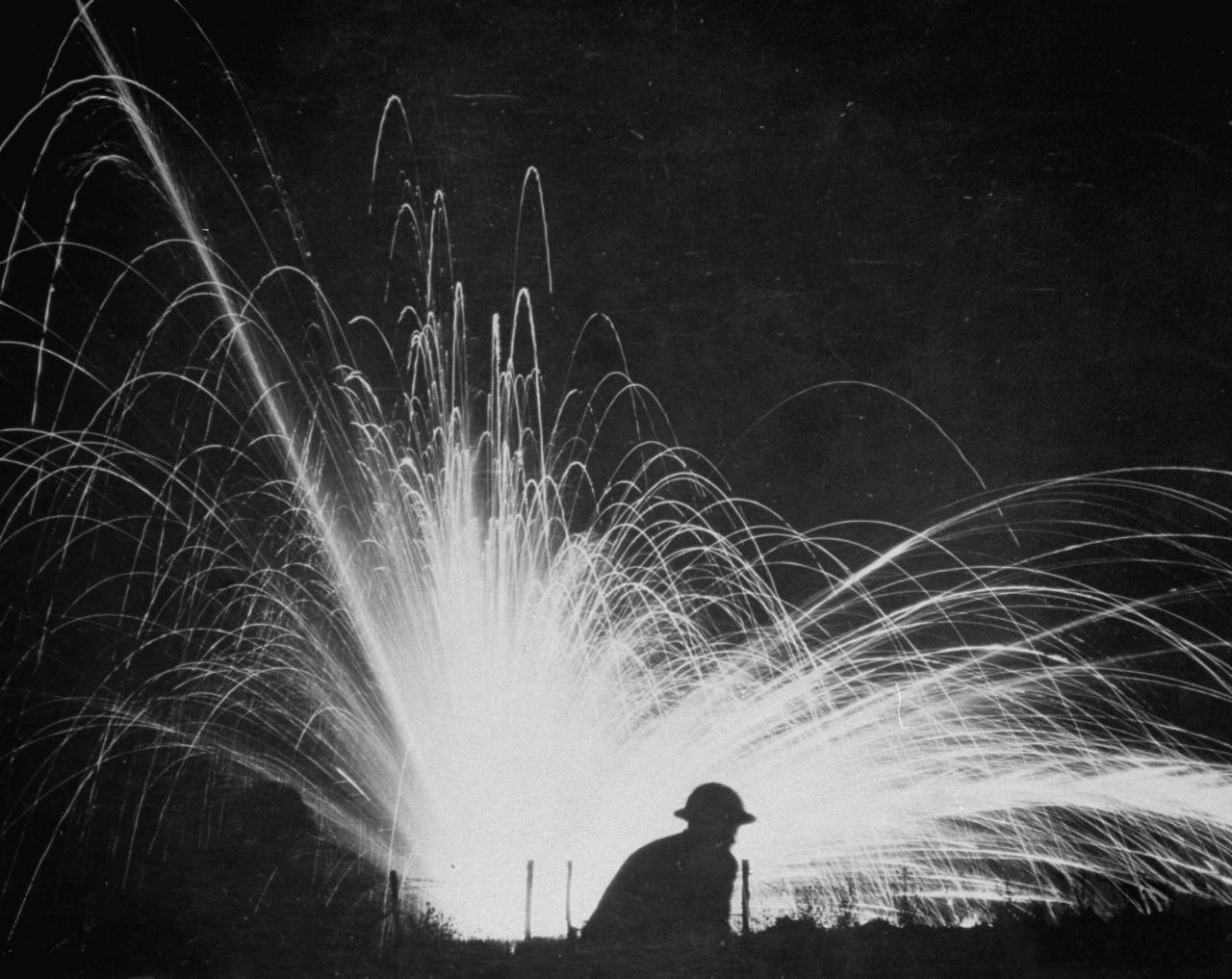 Allied soldier silhoutted by the glare of an exploding phosphorus bomb, 1917