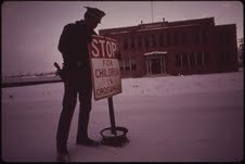 Patrolman Mark Shearer, Rifle, Colorado, puts up school crossing signs at daybreak …, Jan. 1973. Photo by David Hiser.