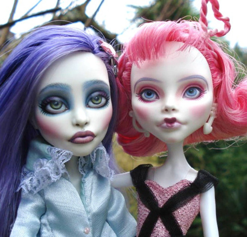 Monster High Spectra Vondergeist and Cupid repaints. Spectra's eyes are green, and she's been given heavy eye and lip makeup, as well as blush that emphasizes her glass-cutting cheekbones. Cupid's eyes are blue and her makeup is pink, and much softer than Spectra's. Customs by Viktoria La Paz.