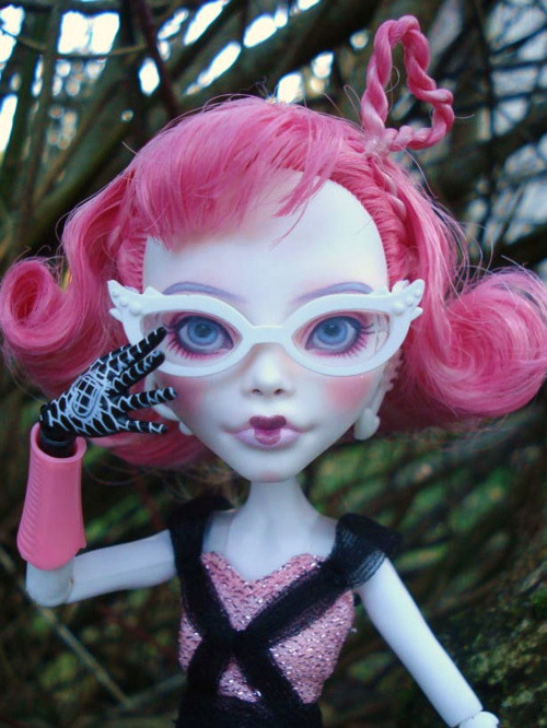 Monster High Cupid repaint. Cupid's been given blue eyes and softer makeup in shades of pink, her cupid's-bow mouth still in evidence but a bit softer than the stock. She's wearing basic Ghoulia's white cat-eye glasses and her own stock outfit, and has one hand raised to eye level. By Viktoria La Paz.