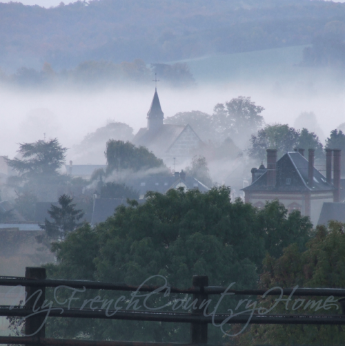 a village in the countryside, with the fog and the church at the center