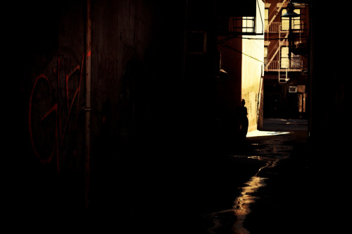 "nythroughthelens:  Lower East Side alley. New York City. In the darkest canals of the city where light seeps through slowly, wanderers emerge bleary-eyed into the sun: birthed explorers carrying darkness into the light. —- There is a solitary aspect to living in such a highly populated city such as New York City. It's easier to sink into the shadows. People pass in stairways and on sidewalks with vigorous abandon : ghosts brushing shoulders in a daily anonymous tango. —- View this photo larger and on black on my Google Plus page —- Buy ""In the Shadows - Lower East Side Alley - New York City"" Prints here, email me, or ask for help."