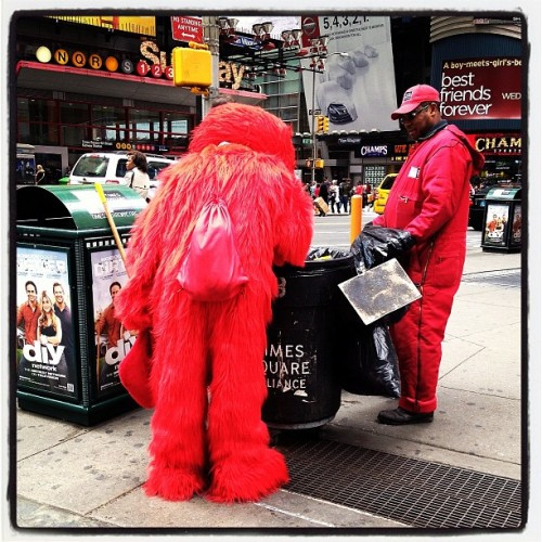 sullyfoto:  Elmo digs through the trash @ Times Square, NYC  My friend Justin has been using his Instagram to document those creepy guys dressed up as Elmo who wander around NYC tourist traps. You should follow him on Tumblr and Instagram @sullyfoto