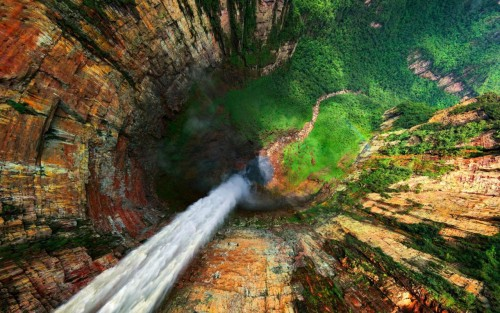 Aerial view of a waterfall. This stunning photograph has lots of depth, and the line of the waterfall draws your eyes down this depth, to the greenery below.
