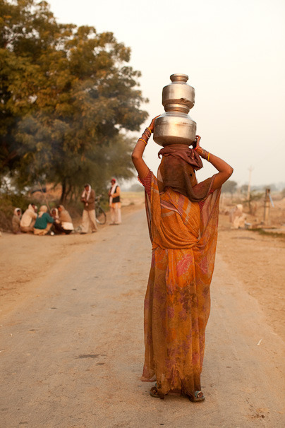 A woman walks home after getting clean water to drink and cook with at her local water well.  The Adventure Project has a new spin on the water crisis. Learn more about solutions that bring long-term impact and flowing water to men, women, and children in India: www.theadventureproject.org