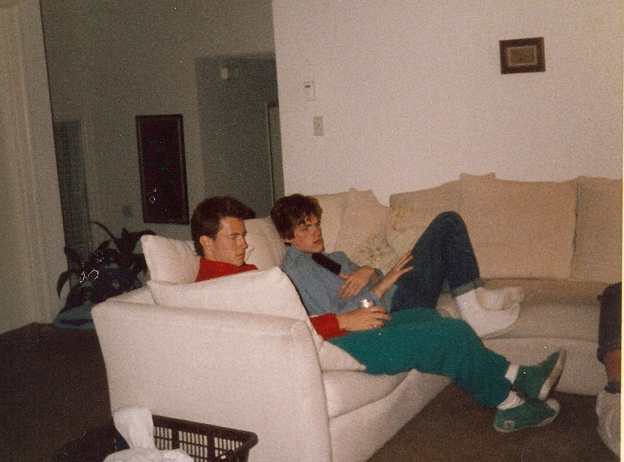 SEAN PATRICK KELLY JASON O'DONNELL TRAEGER COUCH POTATOES SAN DIEGO 1985 Sean Kelly is one of those guys.  Like all my very best friends we're a little different and a lot alike. If someone asked me to tell my best Sean Kelly story I'd ask them if they were kidding. There are just too many good ones. I've known Sean since we were teens. This photo was taken when he joined my family for a while in high school. He may have moved out of the house but as far I'm concerned he's never stopped being a part of the family.  I'll tell a Sean Kelly story in a future post. I can't promise it'll be the best one but you can be sure it'll be a good one! Photo of Sean and me on my mom's couch in Leucadia, CA. from my personal archives.