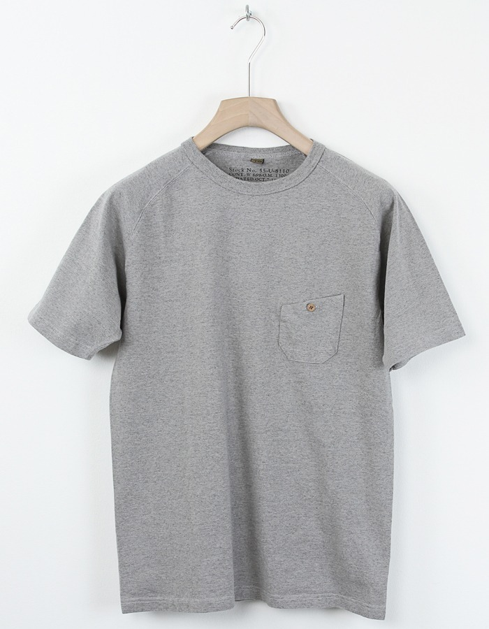 Nigel Cabourn | Basic Pocket Tee Grey Heather Basic Pocket Tee from Nigel Cabourn in Japanese cotton. The t-shirt features a ribbed round neckline, short raglan sleeves and a single buttoned chest pocket. Available to purchase here.
