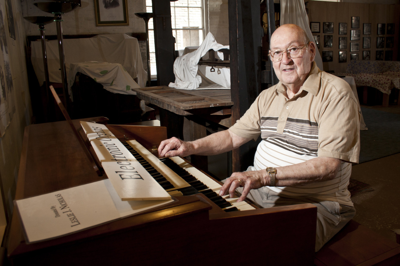 "This is Les Nicholas, a pioneer in the development of electronic organs and former employee of the Estey Organ Company. In this photo he is playing an AS1 Electronic Organ that he built with Harald Bode in 1958, which is on display at the Estey Organ Museum in Brattleboro, Vt. The portrait is to illustrate a story that we are doing about the Estey Organ Museum receiving a donation of another electronic organ that Les built when employed at Estey in the 1950s. Read the story here. The portrait is shot with two strobes. One as the key light attached to a pipe with a ball bungee at camera left. The second strobe is sitting on a bench at camera right and is acting as a fill. Rather than sitting Les down and posing him for this portrait, I asked him to just play a bit for me. My intention is to get a more natural and candid look. Les sat down and started to play commenting that the organ is terribly out of tune. ""Don't worry, you can't hear the photo,"" I say. Purchase photos here."