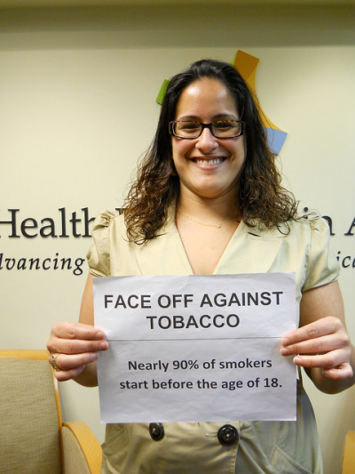 "Face Off Against Tobacco in Dorchester on Flickr.For Daisy, who is working at Health Resources in Action, the ""Face Off Against Tobacco"" campaign is important as a step to prevent youth from smoking.  The quote she is holding up does not surprise her at all: ""When I worked with young people in Roxbury, we surveyed storefront windows on how much tobacco advertisement they have. We found a lot of advertisements that were really colorful, looked like cartoons and candy advertisement, but in fact were for tobacco products. In addition, they were displayed two feet and below so that especially young people could look at them. This was a very concerning thing! We know that advertisement works and therefore this quote is not surprising. The tobacco industry needs to stop targeting young people!"""