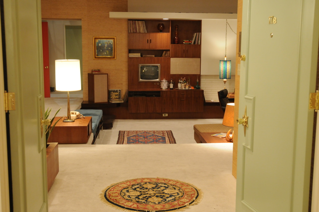 "madmendaily:  Apartment 17-B, right, set decorator Claudette Didul said, is ""in a high-rise that feels like it was built in 1960 with a white-carpeted sunken living room and a fascinating fireplace and a Case Study-style kitchen with two pass through windows."" It also sports walnut cabinetry with a built-in television set and one of those new-fangled-for-the-time push-button phones.  Didul said Draper's love of sleek modern lines and high-tech gadgetry and manly appointments (leather lounge chair, countertop cocktail bar with a drum-shaped ice bucket) is contrasted with his new wife Megan's youthful taste and love of color.  ""I imagine she might've dragged Don through Bloomingdale's to see the model rooms,"" Didul said.  The set decorator also took inspiration from two books by 1960s bestselling interior design author Betty Pepis and ""Decoration U.S.A.,"" a 1965 collaboration between Jose Wilson and Arthur Leaman. ""The colors of the rooms and furnishings are so vibrant in those books they almost make your teeth rattle,"" Didul said."