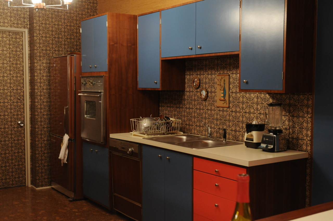 "madmendaily:  The kitchen has rich blue and blazing coral cabinets exhibiting ""happiness and hopefulness,"" Didul said. ""The pastels of the 1950s are giving way to brighter and earthier tones."" She spotted the brown 1964 Frigidaire in a vintage copy of the Los Angeles Times Home Magazine. ""It's my favorite appliance in the whole show."""