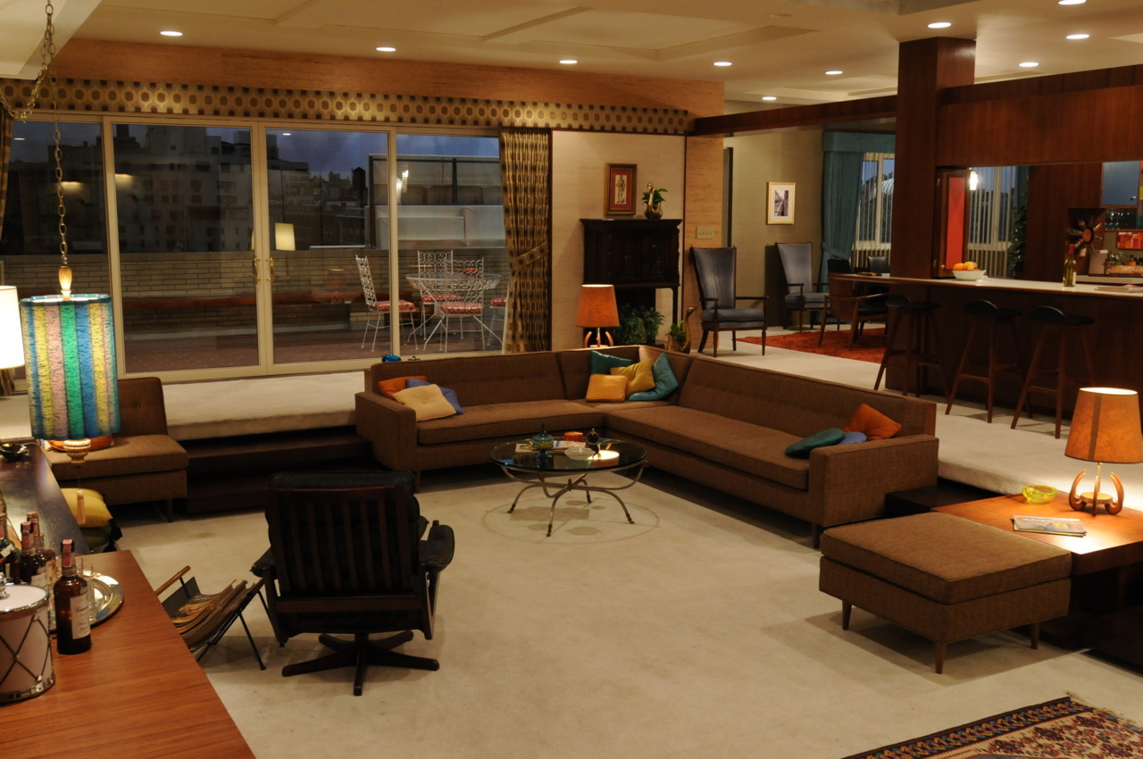 "madmendaily:  The Draper living room has grass cloth wallpaper and curtains with a matching valance made from retro material from Fabricut. Outside the window wall: a 1964 white metal patio dinette set by Samsonite that Didul purchased on eBay. The modular sofas and ottoman were designed by ""Mad Men"" production designer Dan Bishop and built by Omega Cinema Props. Don's Lied Mobler black leather lounge chair came from Galerie Sommerlath in Los Angeles; the magazine rack is fromAmsterdam Modern, also in L.A. The glass-topped coffee table is from Deja Vu in Long Beach, and the counter stools are a vintage design by Erik Buk purchased on Craigslist from a Virginia seller."