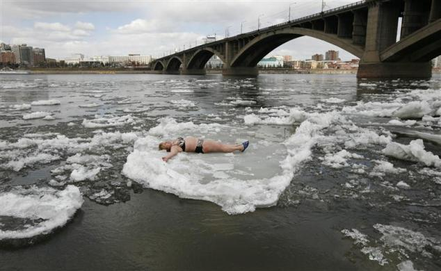 Krasnoyarsk, Russia A member of the Cryophil winter swimmers club lies on floating ice from the spring melting on the Yenisei River (via Reuters.com)