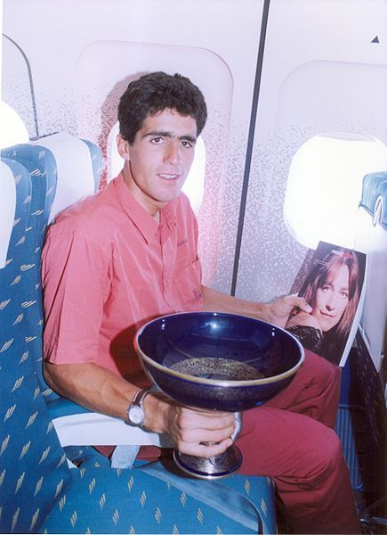 inrng:  Miguel Indurain holds an Iberia in-flight magazine and the Tour de France winner's trophy as he flies home in late July 1991.  Dude. Spashed out in red denim like a boss.